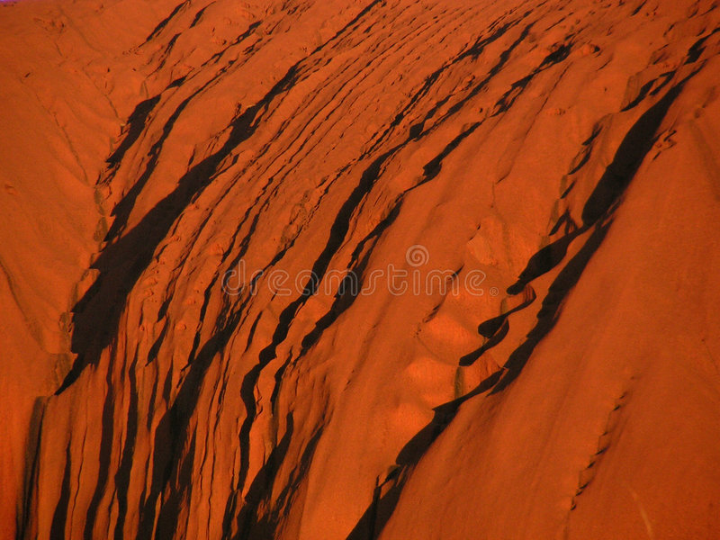 Ayers Rock - Uluru. Detail of the red Ayers Rock / Uluru in the red centre of Australia, glowing in the light of the sunset stock photos