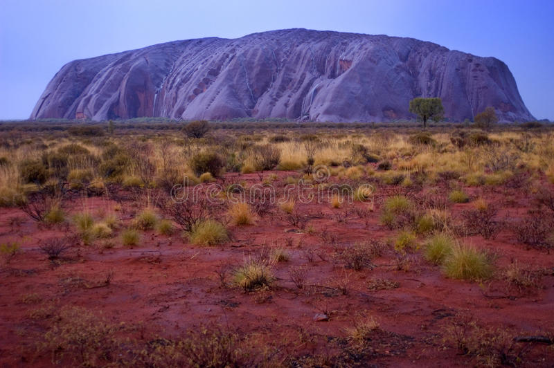 Ayers Rock: Uluru After The Rain Storm Passed. Uluru (Ayers Rock) is famous for its red and orange glow at sunrise and sunset, but the Australian Outback comes royalty free stock photography