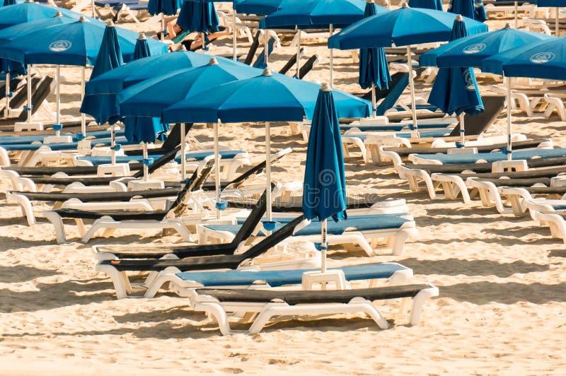 Ayia Napa,塞浦路斯- 08 08 2008年:蓝色伞和轻便马车休息室一个公开海滩的在一个夏天早晨 海上的一个安静的假期 库存图片