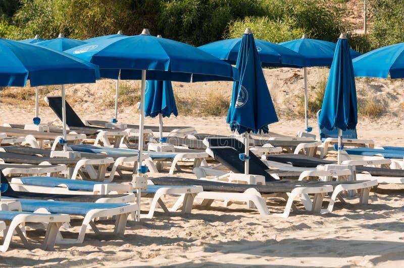 Ayia Napa, Chipre - 08 08 2008: paraguas y salones azules de la calesa en una playa pública en una mañana del verano Vacaciones r imagen de archivo