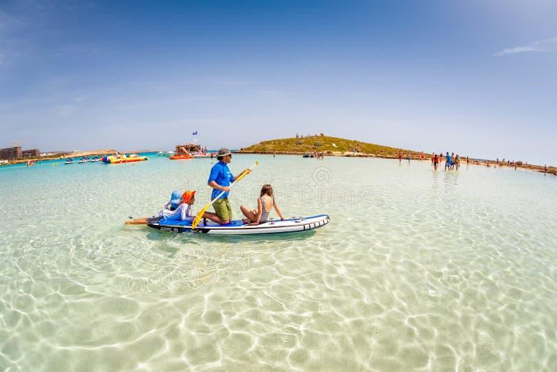 AYIA NAPA, CIPRO - 7 APRILE 2018: Generi con i bambini che si divertono sopra stanno sul bordo di pagaia alla spiaggia di Nissi fotografia stock