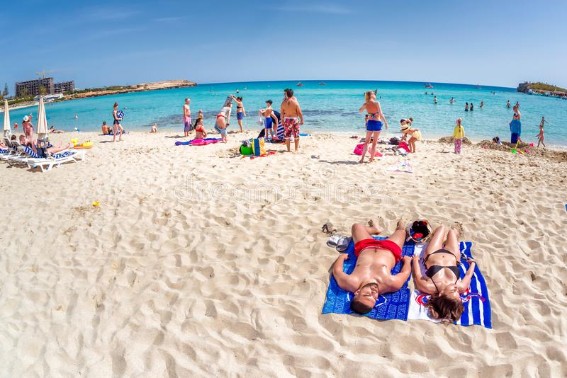 AYIA NAPA CYPERN - APRIL 07, 2018: Folk som lägger på stranden royaltyfria bilder