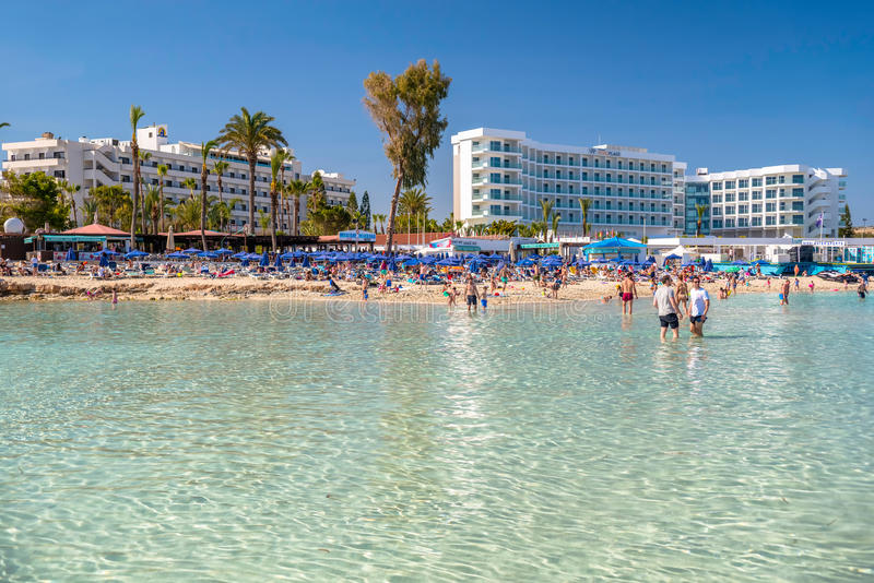 AYIA NAPA, CYPRUS - April 04, 2016: People swimming and sunbathing on the picturesque Nissi beach stock image