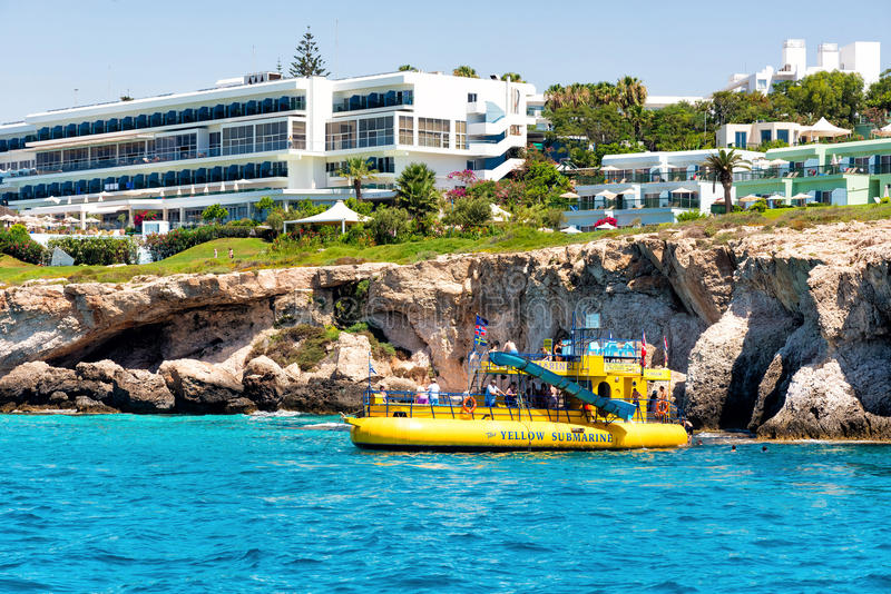 AYIA NAPA, CYPRUS - JULY 16, 2016: Recreational boat with tourists near the rocky cliffs of Cavo Greco near Ayia N. Apa. Famagusta District, Cyprus royalty free stock photos
