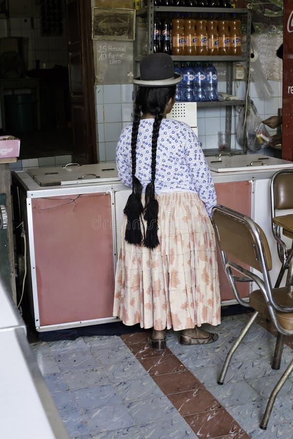 Aymara kobieta Z Długimi warkoczami, Jest ubranym Klasycznego dęciaka kapeluszu czekanie Przy lody sklepem zdjęcia stock