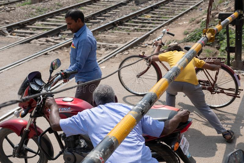 Ayodhya, Uttar Pradesh / India - April 2, 2019: Blatantly ignoring the train signals, users of the road cross the train tracks any stock images