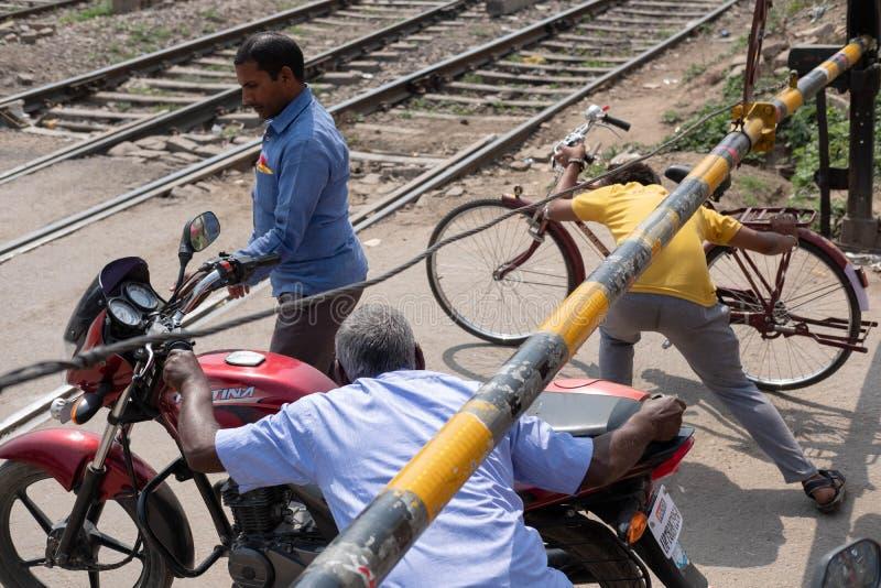 Ayodhya Uttar Pradesh/Indien - April 2, 2019: Uppenbart ignorera drevsignalerna, korsar användare av vägen drevspåren  arkivbilder