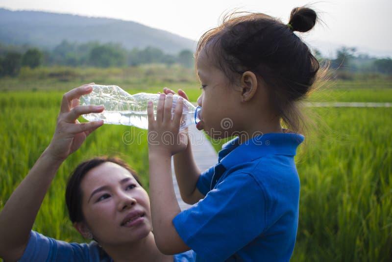 Ayuda de la madre su agua potable de los niños de la botella en campo del arroz muchacho largo del pelo imagen de archivo libre de regalías