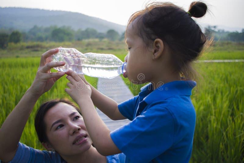 Ayuda de la madre su agua potable de los ni?os de la botella en campo del arroz muchacho largo del pelo fotografía de archivo