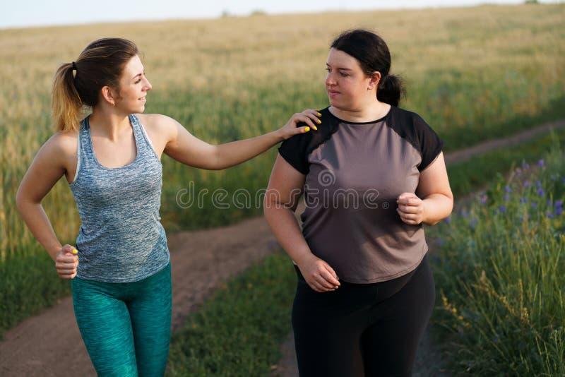 Ayuda de la mujer del ajuste y motivar al amigo en el entrenamiento fotos de archivo