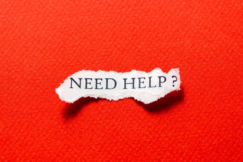 Ayuda de la necesidad en el pedazo del rojo del papel imágenes de archivo libres de regalías