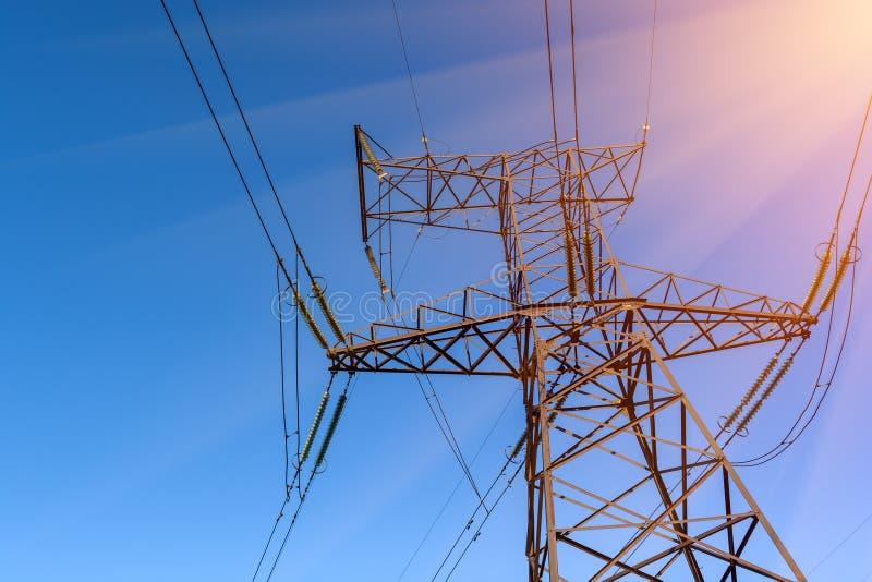 Ayuda de las electro líneas de transmisión contra el cielo azul imagenes de archivo