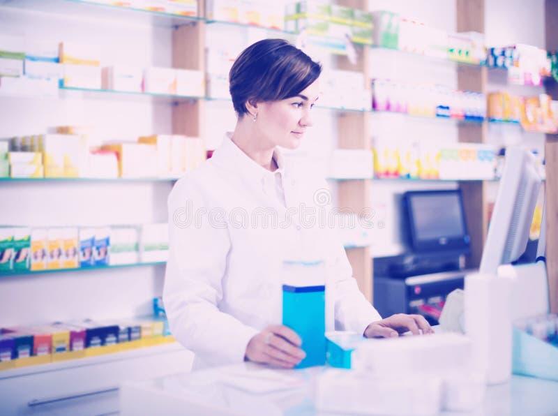 Ayuda de ofrecimiento del farmacéutico de sexo femenino en el contador en farmacia foto de archivo