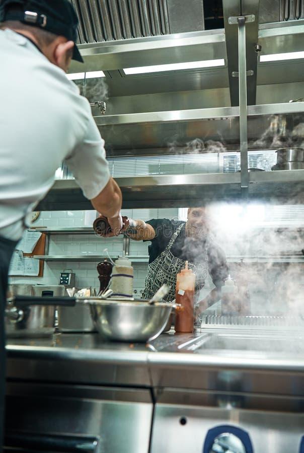 Ayuda en cocina Foto vertical del cocinero profesional joven que da una amoladora de pimienta a su ayudante mientras que cocina imagenes de archivo