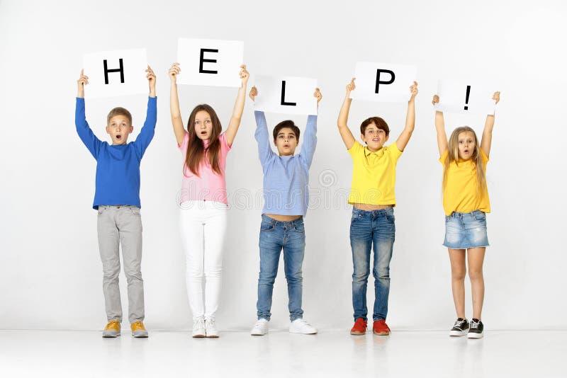 ayuda Grupo de niños con banderas aisladas en blanco imagen de archivo