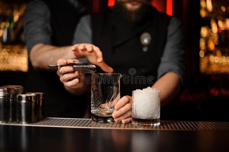 Ayuda profesional del camarero a otra que hace un cóctel fotos de archivo