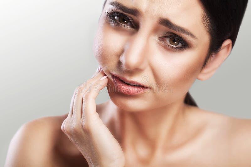 Ayuda y dolor de muelas de Stomatologic Una mujer joven enseña a una muchacha que sufra de un dolor terrible en sus dientes, toca fotos de archivo libres de regalías