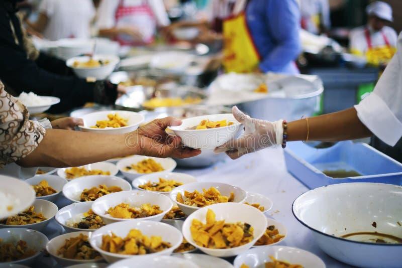 Ayudan al vagabundo con el alivio de comida, alivio del hambre: un concepto social de distribución imagenes de archivo