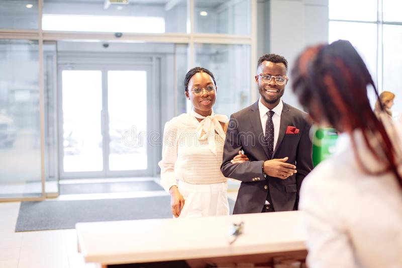 Ayudante africano del alquiler de coches que da la información a un cliente de los pares imágenes de archivo libres de regalías
