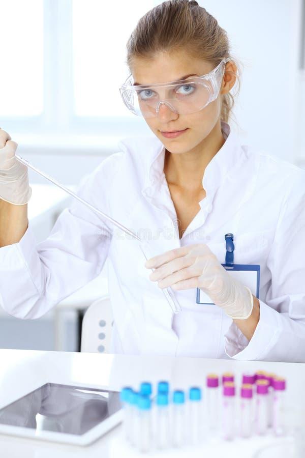 Ayudante científico femenino del investigador o del análisis de sangre en el trabajo en laboratorio Concepto de la ciencia, de la foto de archivo