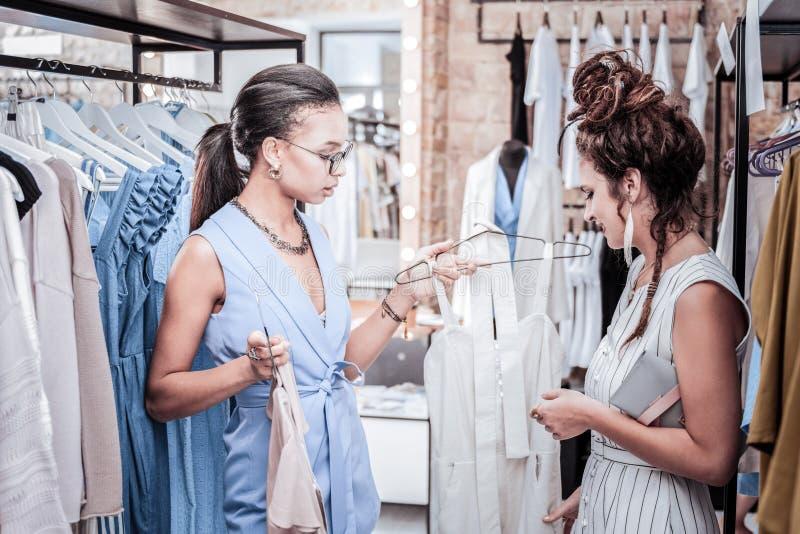 Ayudante de compras que ofrece sus variantes constantes del cliente de los vestidos del verano foto de archivo