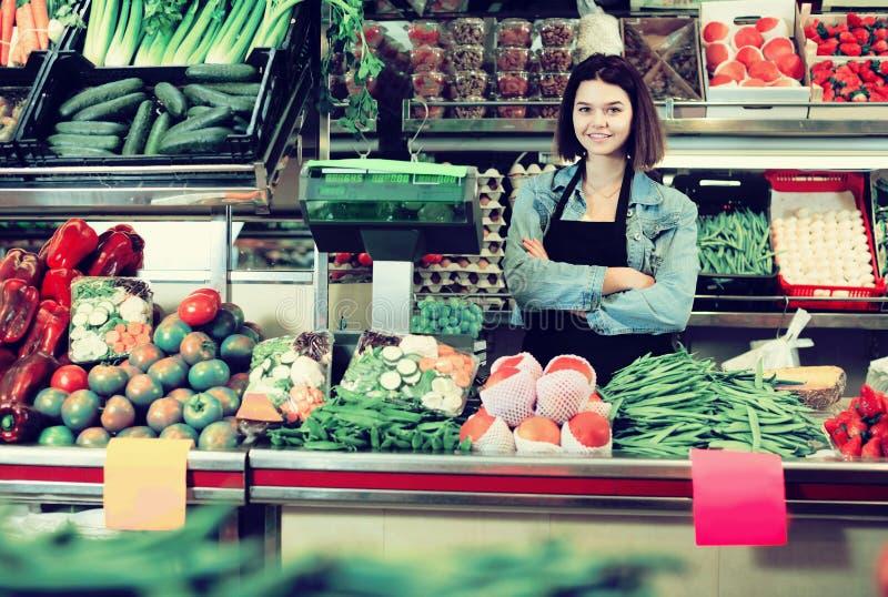 Ayudante de compras que pesa la fruta y verdura en tienda de ultramarinos fotos de archivo