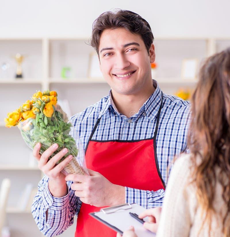 Ayudante de florister?a que vende las flores al cliente femenino imagen de archivo