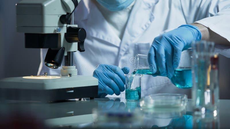 Ayudante de laboratorio que vierte el reactivo líquido en el cubilete para crear la solución química imagenes de archivo