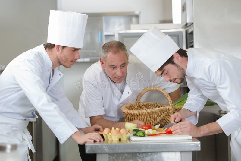 Ayudante de observación del principal cocinero que adorna el plato imagen de archivo