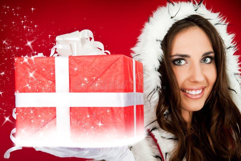 Ayudante de Santas que lleva a cabo el regalo de Navidad brillante imagen de archivo