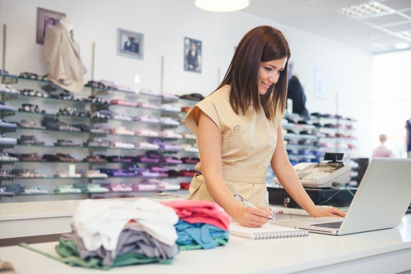 Ayudante de tienda en una tienda de la ropa foto de archivo
