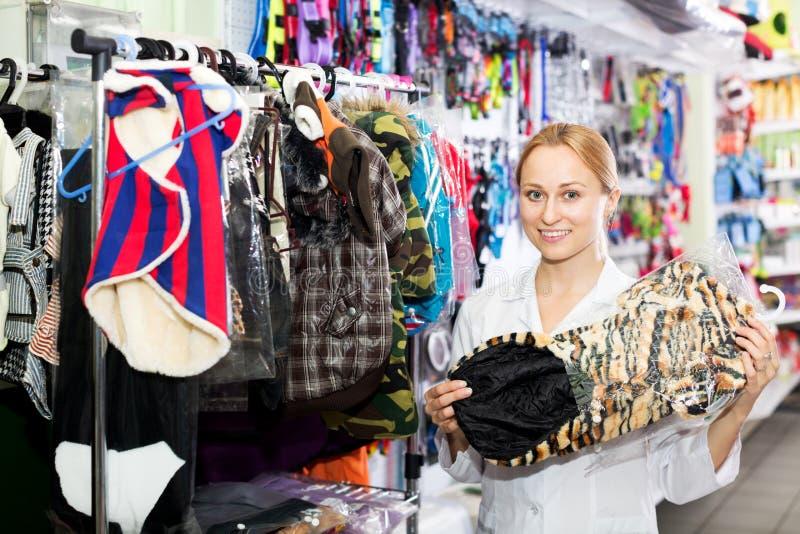 Ayudante de tienda femenino que muestra la ropa para los animales domésticos fotografía de archivo