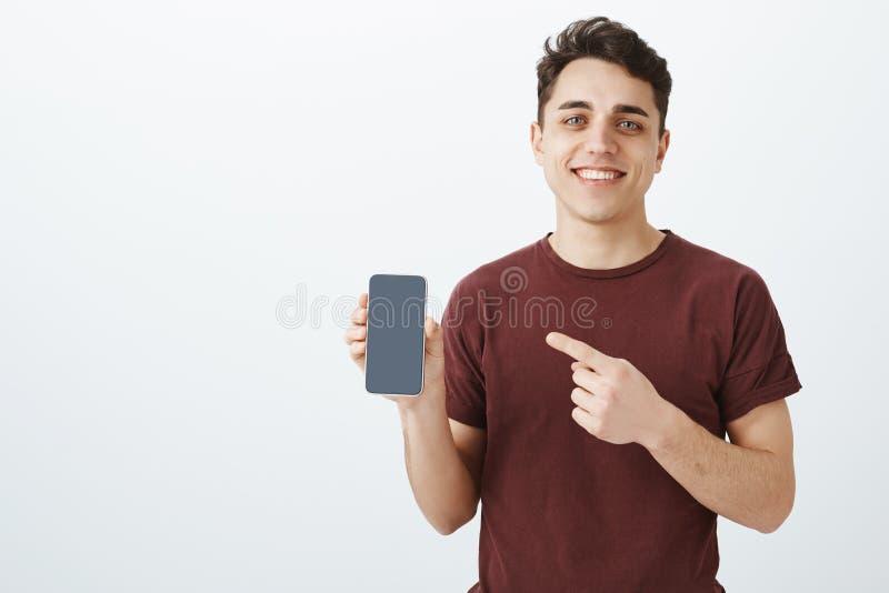 Ayudante de tienda masculino amistoso apuesto en la camiseta roja casual, mostrando smartphone a estrenar y señalando en el dispo imágenes de archivo libres de regalías