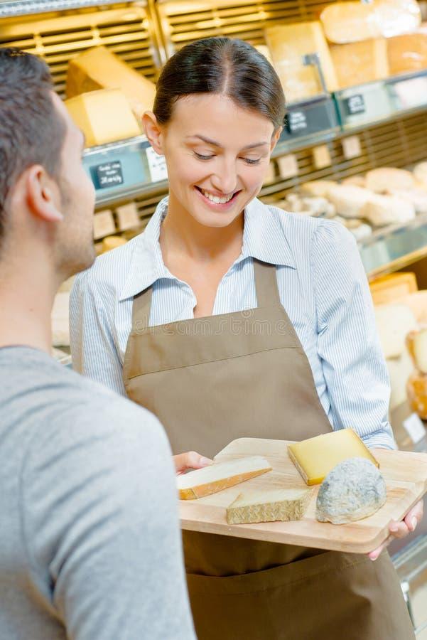 Ayudante de tienda que muestra los quesos de la bandeja del cliente foto de archivo