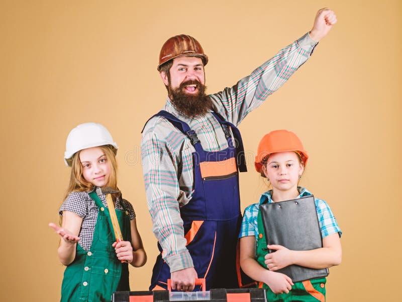 ayudante del trabajador de construcci?n Constructor o carpintero Hombre barbudo con las ni?as reparaci?n La creatividad de los ni fotografía de archivo libre de regalías