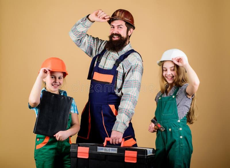 ayudante del trabajador de construcci?n Constructor o carpintero Reparador en uniforme Ingeniero Hombre barbudo con las ni?as fotografía de archivo libre de regalías