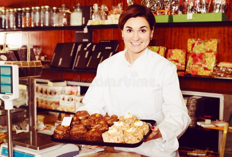 Ayudante femenino positivo que demuestra las tortas deliciosas imagen de archivo