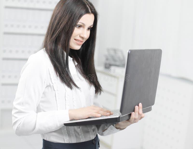 Ayudante femenino que usa el ordenador portátil que se coloca en oficina fotos de archivo libres de regalías