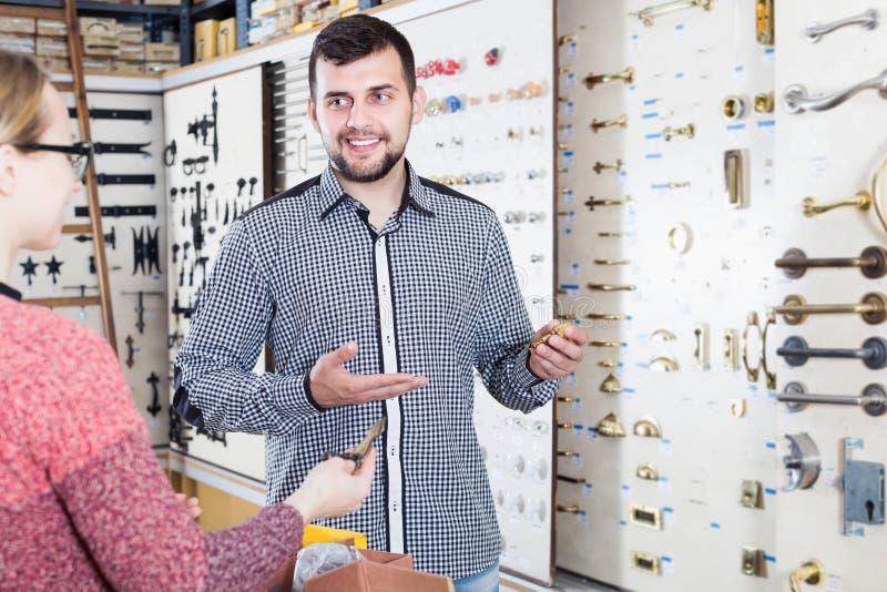 Ayudante que ayuda al cliente femenino a elegir los tiradores de puerta imagen de archivo libre de regalías