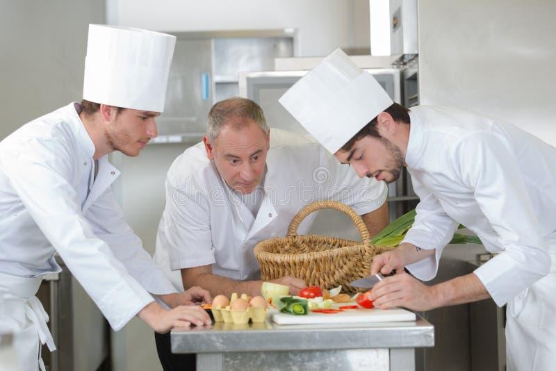 Ayudantes de observación del principal cocinero que adornan el plato imagen de archivo libre de regalías
