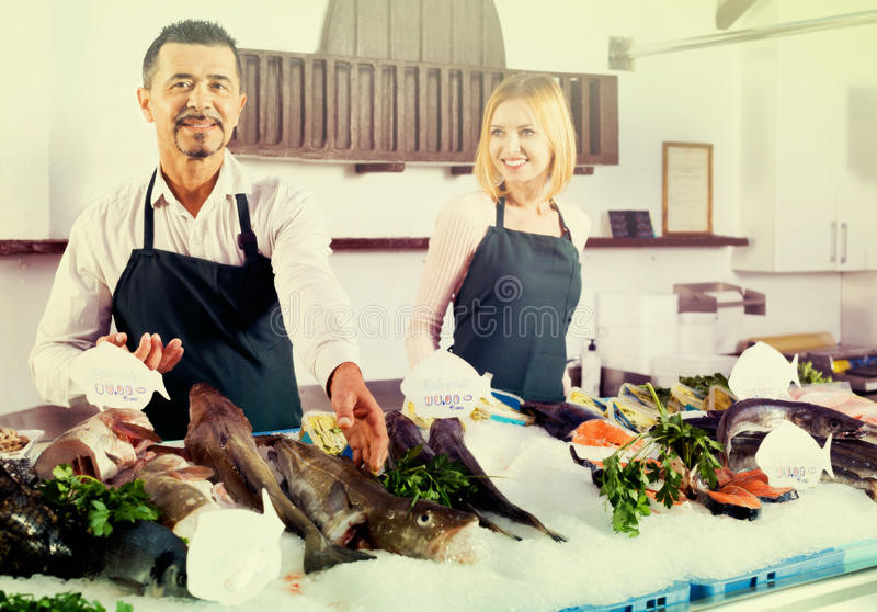 Ayudantes de tienda alegres positivos que venden pescados frescos imagen de archivo