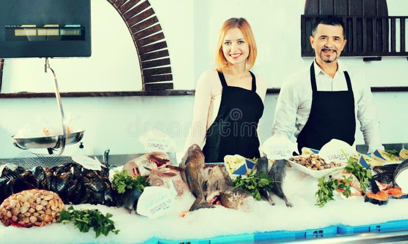 Ayudantes de tienda alegres sonrientes que venden pescados frescos foto de archivo
