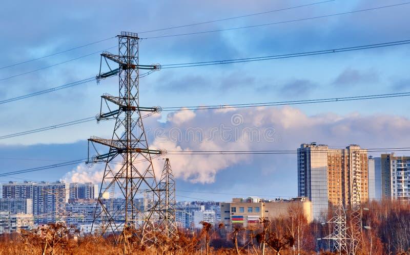 Ayudas de las líneas eléctricas de alto voltaje, casas modernas, caminos, tubos que fuman En el primero plano están los árboles s fotos de archivo libres de regalías