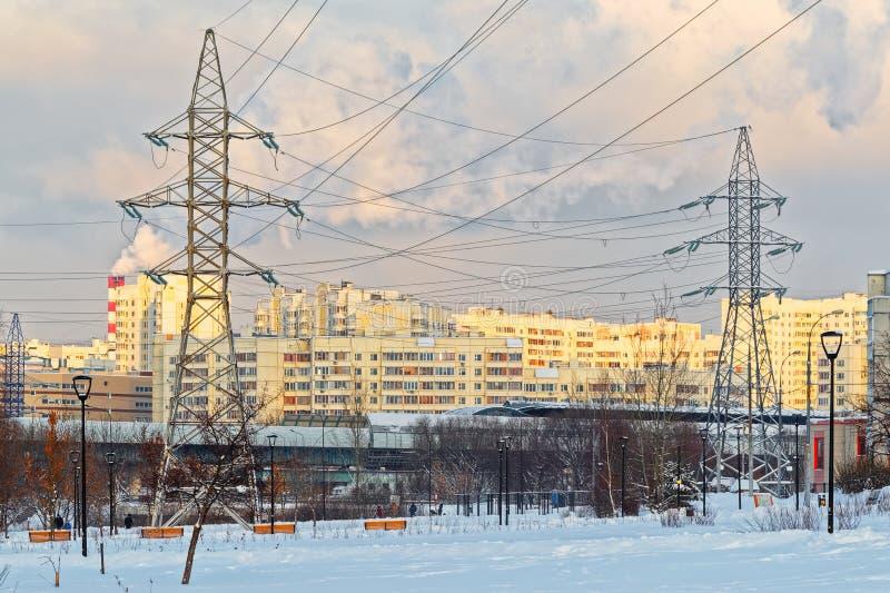 Ayudas de las líneas eléctricas de alto voltaje, casas modernas, caminos, tubos que fuman En el primero plano están los árboles s foto de archivo
