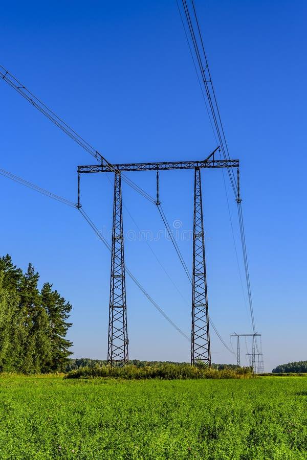 Ayudas del metal y cables de una línea de transmisión de alto voltaje sobre un campo verde por la mañana del comienzo del verano imágenes de archivo libres de regalías