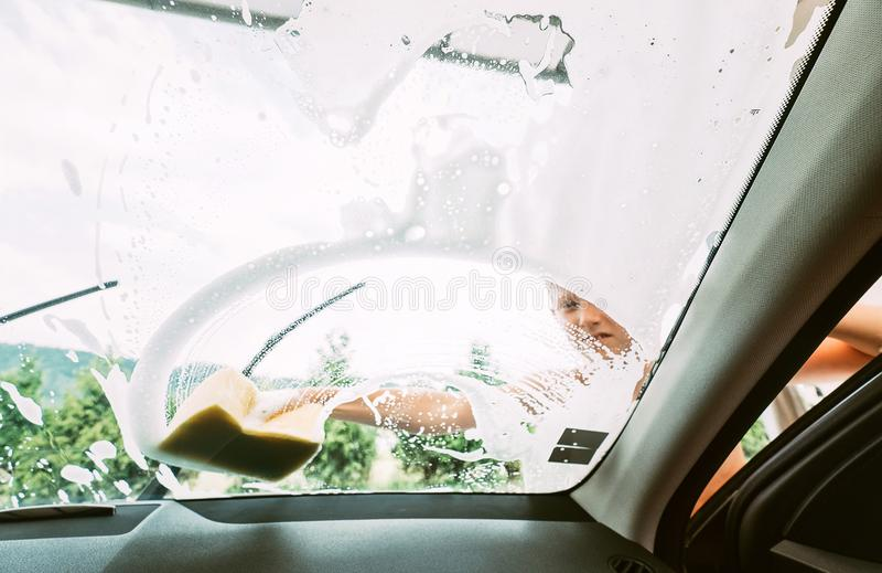 Ayudas del muchacho para lavar un coche Opinión interior de la cámara del coche fotografía de archivo