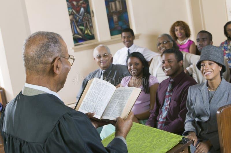 Ayude a Giving Sermon a la congregación en la opinión de la parte posterior de la iglesia fotografía de archivo libre de regalías