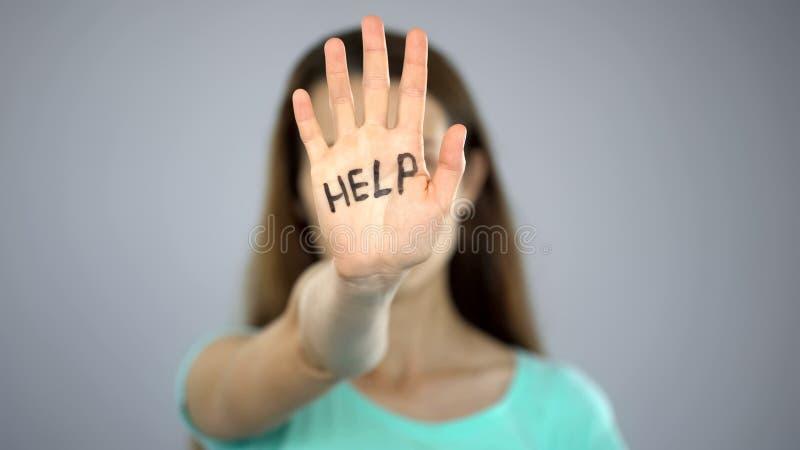 Ayude a la muestra en la mano de la mujer, víctima que pide la ayuda, asalto en familia, conciencia imagenes de archivo