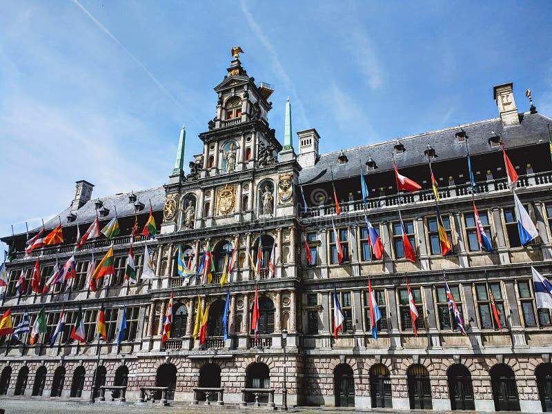 Ayuntamiento Amberes adornado con las banderas internacionales capturadas durante día soleado imagenes de archivo