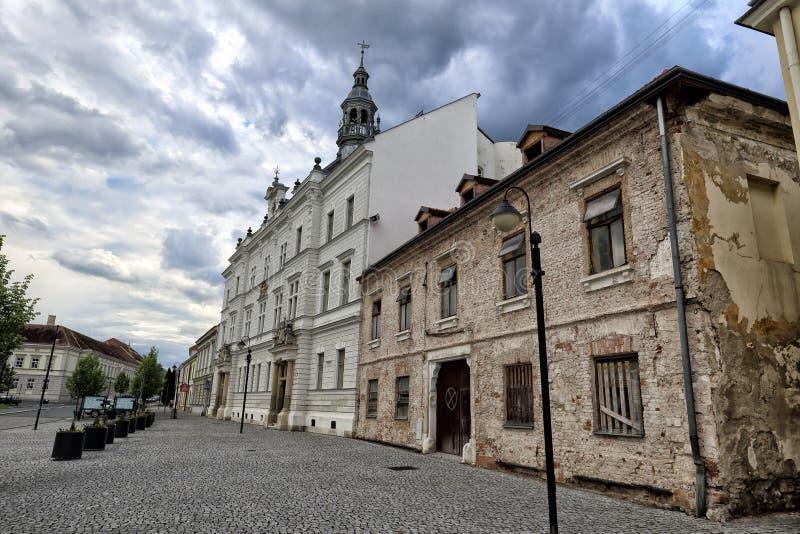 Ayuntamiento blanco de Valtice y de la casa abandonada foto de archivo libre de regalías